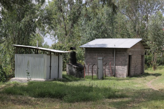 The corrugated iron structure is a pit latrine at Kolladiba Health Centre. It is locked, but I cannot fathom why. As soon as one urinates into the hole, clouds of mosquitoes emerge, looking for dinner.